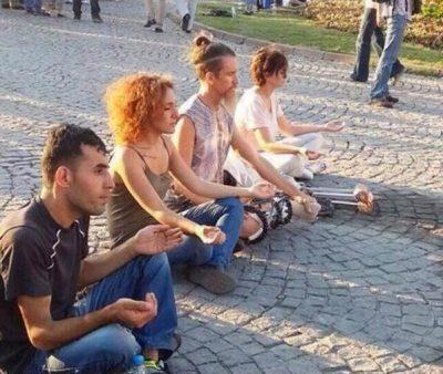Yoga yapanların yanında oturup dua eden gariban yu